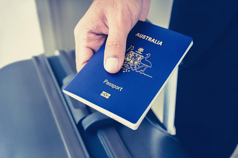 Hands giving passport of Australia to electronic reader