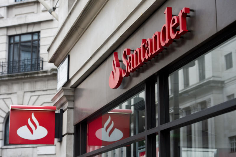 "Embargoed to 0001 Monday July 15 File photo dated 14/02/15 of Santander signage above a branch. The high street lender is rolling out its global ""work cafe"" chain to the UK with a site in Leeds offering small businesses and entrepreneurs free co-working spaces and banking facilities."