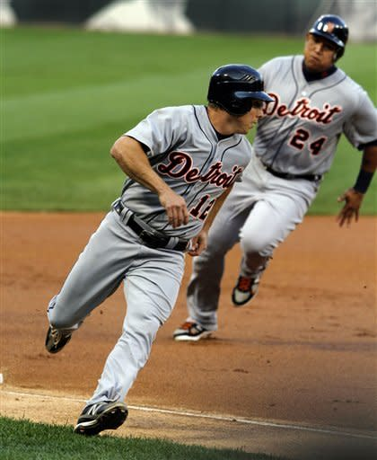 Detroit Tigers' Andy Dirks (12) and Miguel Cabrera (24) round third and score on a double by Prince Fielder in the first inning of a baseball game against the Chicago White Sox, Monday,May 14, 2012, in Chicago. (AP Photo/John Smierciak)
