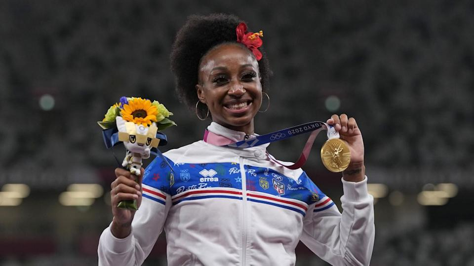 Jasmine Camacho-Quinn holds up flowers and the gold medal around her neck.