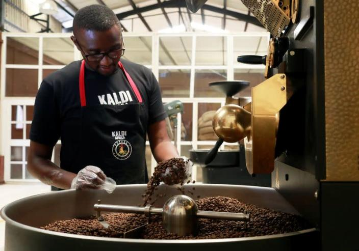 An employee checks freshly roasted coffee beans during cooling down in a tumbler at Kaldi Africa coffee roastery in Lagos
