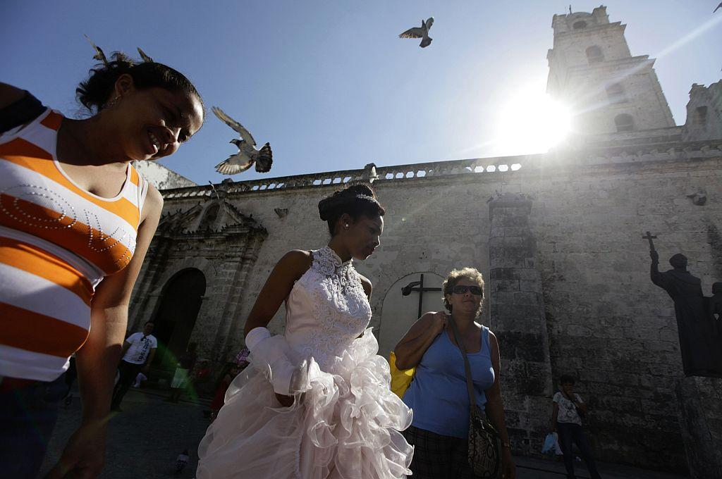 <p>Carmen Gonzalez (C) walks with her mother Marlen (L) for a photo session in the old quarters of Havana for her quinceanera (coming-out for 15-year-olds) celebration.</p>