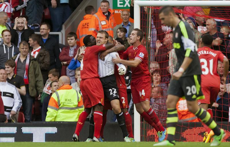 Liverpool's goalkeeper Simon Mignolet, centre, celebrates with teammates after saving a penalty during his team's English Premier League soccer match against Stoke City, at Anfield Stadium, Liverpool, England, Saturday Aug. 17, 2013. (AP Photo/Jon Super)