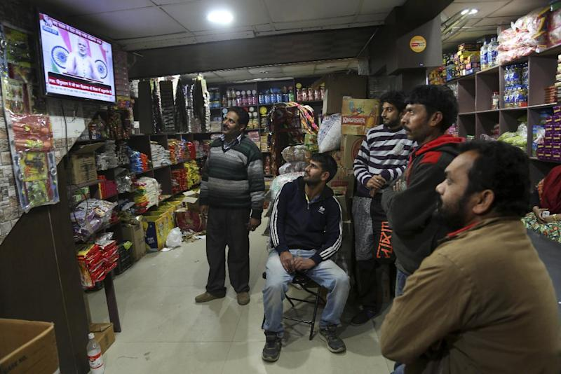 People watch Indian Prime Minister Narendra Modi addressing the nation, on television at a grocery store in Jammu, India, Saturday, Dec. 31, 2016. A day after the deadline for depositing old 500- and 1,000-rupee notes, Modi called the demonetization a purification drive during his Saturday speech. (AP Photo/Channi Anand)