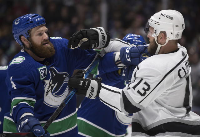 Vancouver Canucks' Jordie Benn, left, and Los Angeles Kings' Kyle Clifford shove each other after the whistle during the first period of an NHL hockey game Wednesday, Oct. 9, 2019, in Vancouver, British Columbia. (Darryl Dyck/The Canadian Press via AP)