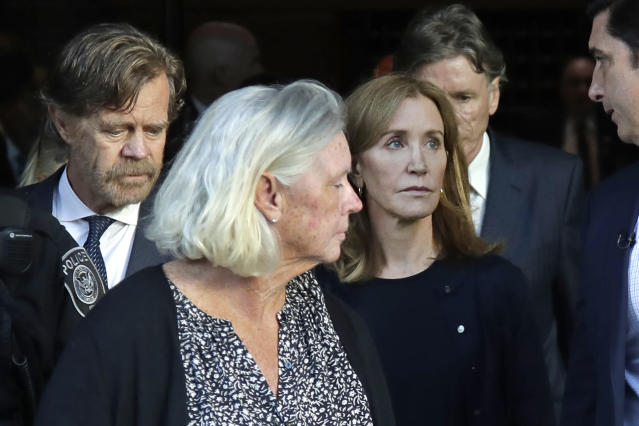 Felicity Huffman, right, leaves federal court with her husband William H. Macy, far left, after her sentencing in a nationwide college admissions bribery scandal, Friday, Sept. 13, 2019, in Boston. (AP Photo/Elise Amendola)