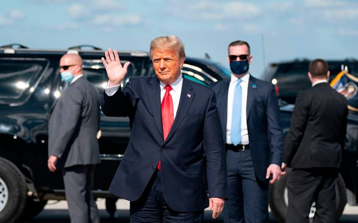 Outgoing US President Donald Trump waves after landing at Palm Beach International Airport in West Palm Beach, Florida - AFP