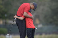 Tiger Woods, left, shares an embrace with his son Charlie after finishing on the 18th green during the final round of the PNC Championship golf tournament, Sunday, Dec. 20, 2020, in Orlando, Fla. (AP Photo/Phelan M. Ebenhack)