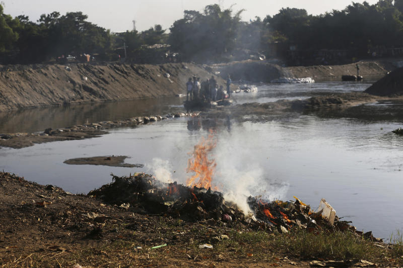 Trash left behind by Central American migrants is burned, set fire by locals who operate the small ferries on the Suchiate River near Ciudad Hidalgo, Mexico, Friday, Jan. 24, 2020, a location popular for migrants to cross from Guatemala to Mexico. (AP Photo/Marco Ugarte)