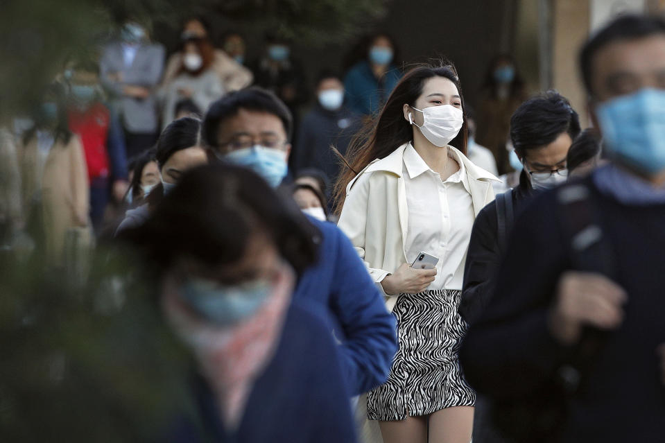 Commuters wearing face masks to help curb the spread of the coronavirus walk out from a subway station during the morning rush hour in Beijing, Tuesday, Oct. 27, 2020. (AP Photo/Andy Wong)