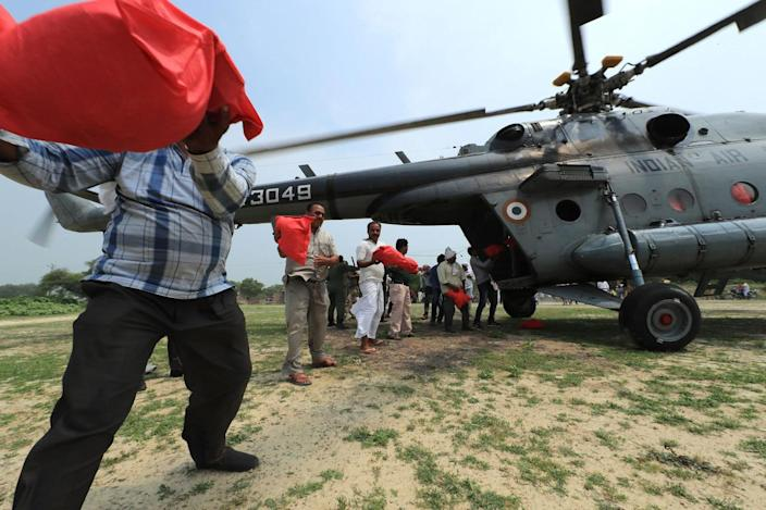 <p>Flood affected villagers queue up to unload relief material from Indian Air Force helicopter on the outskirts of Allahabad, India, Friday, Aug. 26, 2016. (AP Photo/Rajesh Kumar Singh)</p>