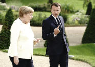 German Chancellor Angela Merkel, left and French President Emmanuel Macron talk in the garden of Meseberg Castle, the German government's guest house in Meseberg, Germany, Monday, June 29, 2020. Merkel met Monday with French President Emmanuel Macron for talks as Germany prepares to take over the European Union presidency. (Kay Nietfeld/dpa via AP)