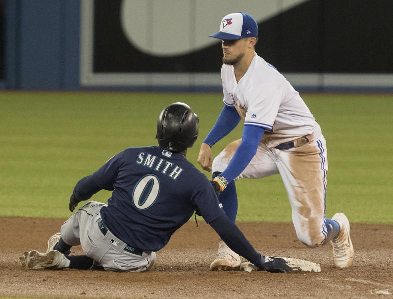 Seattle Mariners' Mallex Smith is tagged out by Toronto Blue Jays' Cavan Biggio while trying to stretch a single into a double during the eighth inning of a baseball game Friday, Aug. 16, 2019, in Toronto. (Fred Thornhill/The Canadian Press via AP)