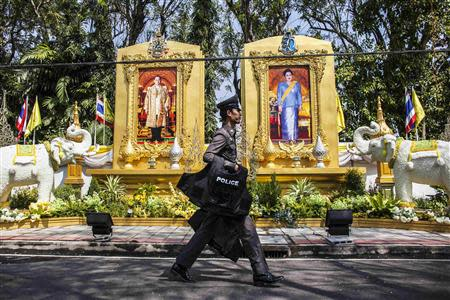 A policeman carries protective gear as he walks next to the residential house of Prem Tinsulanonda, chief of the Privy Council and the king's advisor, in Bangkok January 24, 2014. REUTERS/Nir Elias