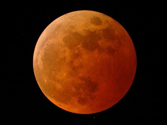 The moon appears orange-red in a total lunar eclipse on October 27, 2004.