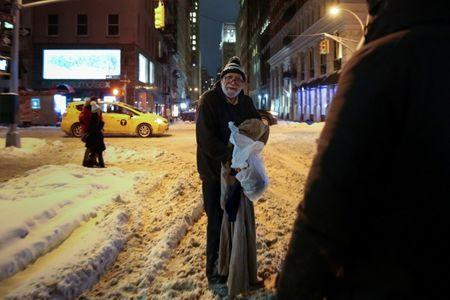 A homeless man smiles after he receives a hot meal and donated clothing as New York City's Coalition for the Homeless delivers food, donated clothing and supplies to homeless people as part of their weekly distribution during winter storm Grayson in Manhattan, New York City, U.S., January 4, 2018. REUTERS/Amr Alfiky