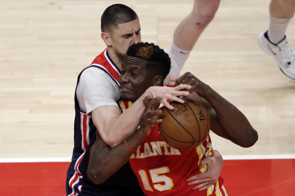 Atlanta Hawks center Clint Capela (15) is fouled by Washington Wizards center Alex Len (27) as he drives to the basket during the first half of an NBA basketball game Wednesday, May 12, 2021, in Atlanta. (AP Photo/Butch Dill)