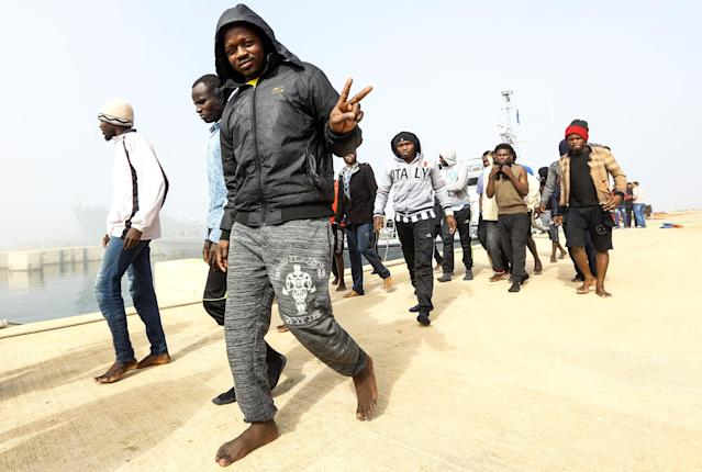 <p>An African migrant flashes the victory gesture after disembarking following his rescue from off the coast of Zawiyah, about 45 kilometres west of the Libyan capital Tripoli, at the dock at the capital's naval base on March 10, 2018. (Photo: Mahmud Turkia/AFP/Getty Images) </p>