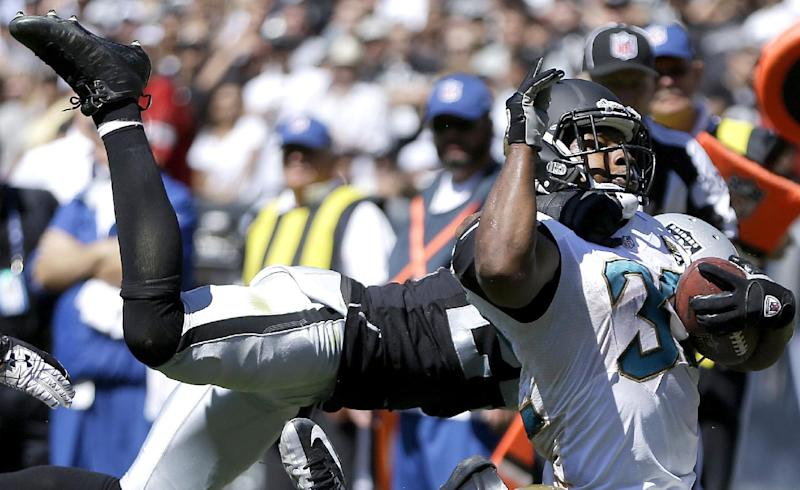 Jacksonville Jaguars running back Maurice Jones-Drew is tackled by Oakland Raiders cornerback Charles Woodson during the second quarter of an NFL football game, Sunday, Sept. 15, 2013, in Oakland, Calif. (AP Photo/Ben Margot)