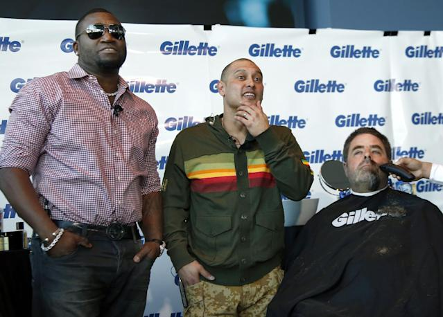Boston Police Officer Steve Horgan is shaved as Boston Red Sox baseball players David Ortiz, left, and Shane Victorino, center, look on during a shave-off for One Fund Boston, the Boston Marathon charity for bombing victims, in Boston, Monday, Nov. 4, 2013. The Red Sox players' beards became a symbol of their solidarity as they went from worst in the AL East last year to first this year by winning the team's third World Series title in a decade. (AP Photo/Elise Amendola)