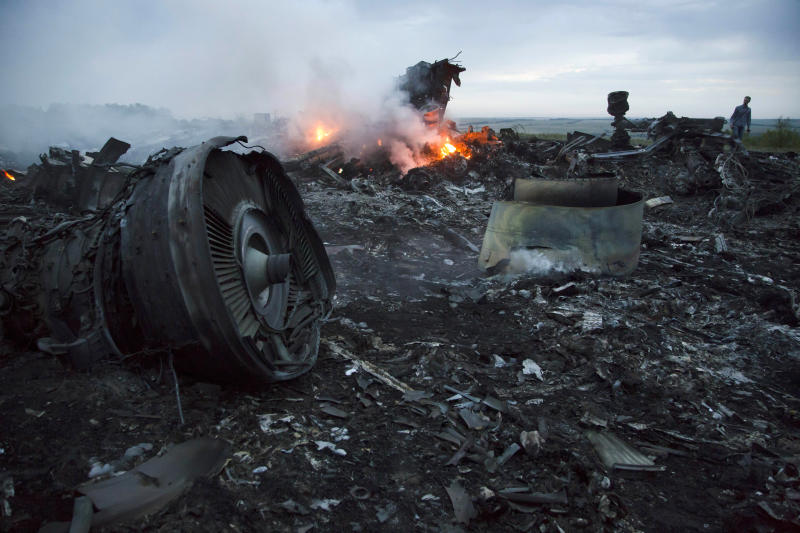 FILE - In this Thursday, July 17, 2014 file photo, a man walks amongst the debris at the crash site of a passenger plane near the village of Hrabove, Ukraine. An international team of investigators building a criminal case against those responsible in the downing of Malaysia Airlines Flight 17 is set to announce progress in the probe on Wednesday June 19, 2019, nearly five years after the plane was blown out of the sky above conflict-torn eastern Ukraine. (AP Photo/Dmitry Lovetsky, File)