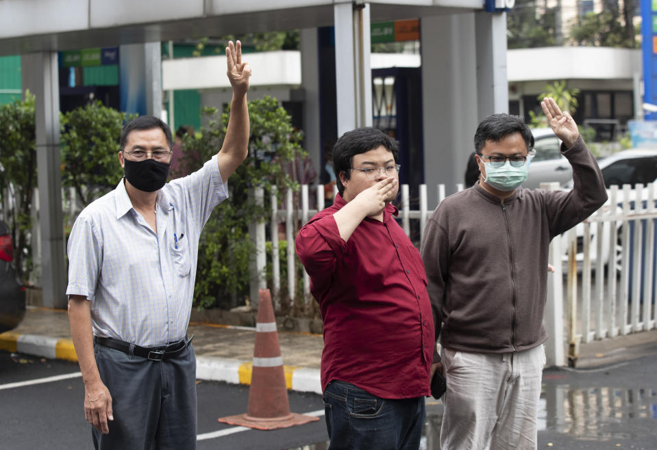 Activist Somyot Pruksakasemsuk, left Parit Chiwarak, and Arnon Nampha raise a three-finger salute, a symbol of resistance, as they arrive at Criminal court in Bangkok, Thailand, Tuesday, Feb. 9, 2021. Four activists, including Somyot, Parit, and Arnon, from Thailand's pro-democracy movement reported themselves to the court on Tuesday as they are formally charge of defaming the monarchy, as the authorities step up legal actions against protesters accused of insulting the royal institution. (AP Photo/Sakchai Lalit)
