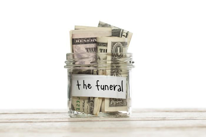 Jar that says the funeral filled with rolled-up dollar bills.