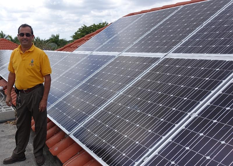 Raul Vergara, president of Cutler Bay Solar Solutions, stands near his latest solar installation on February 20, 2015 at a mansion in Palmetto Bay, Florida (AFP Photo/Kerry Sheridan)