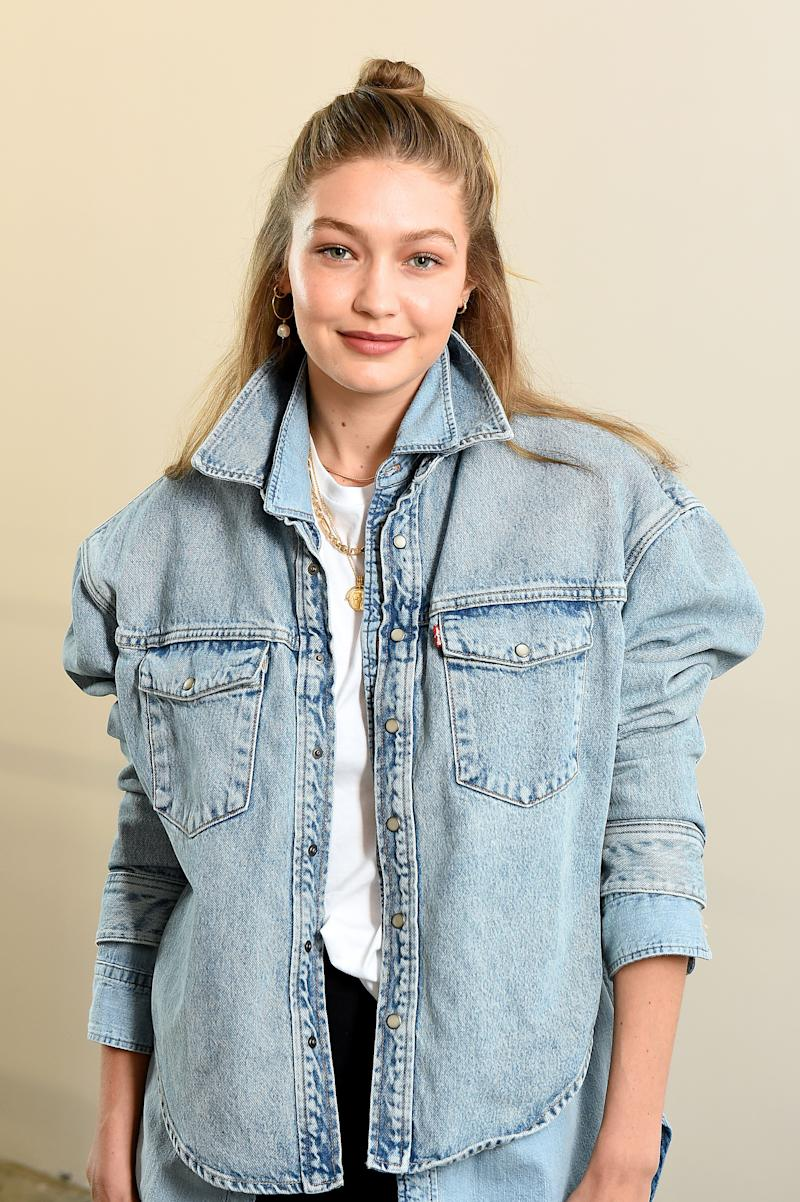 Gigi Hadid looks fantastic in denim jacket and black pant to match as she poses for the camera