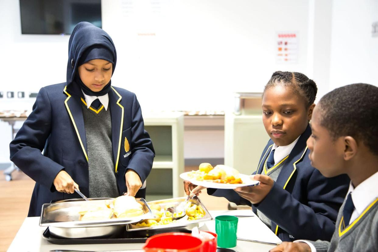 Pupils serve each other as part of Michaela's 'Family Lunch' system