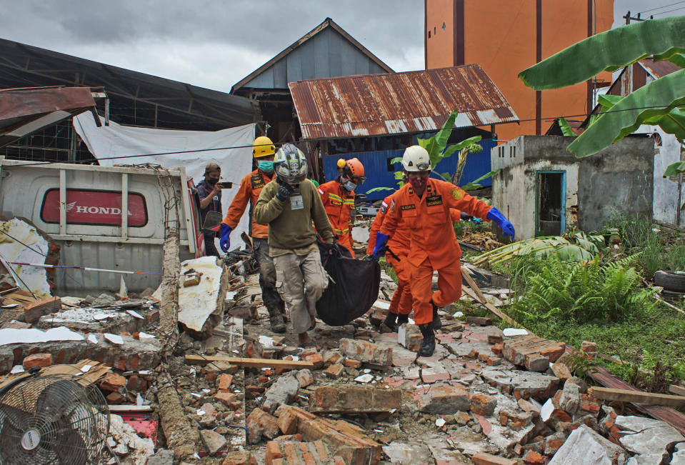 Rescuers carry a body bag containing a victim of an earthquake in Mamuju, West Sulawesi, Indonesia, Friday, Jan. 15, 2021. A strong, shallow earthquake shook Indonesia's Sulawesi island just after midnight Friday, toppling homes and buildings, triggering landslides and killing a number of people. (AP Photo/Azhari Surahman)