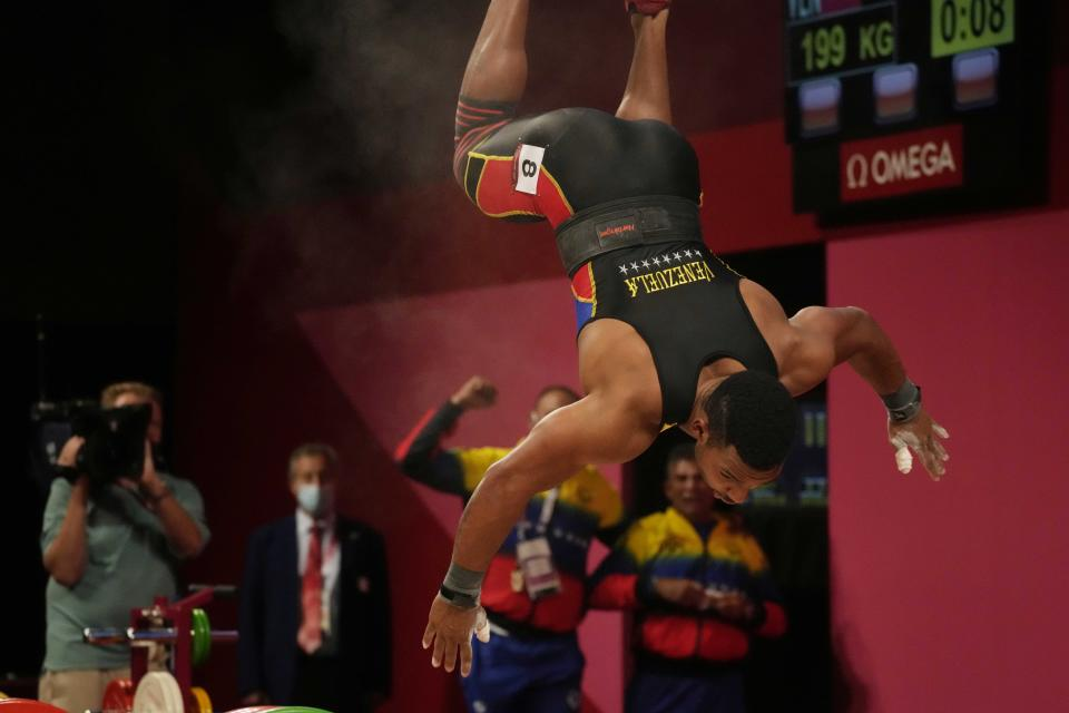 Julio Ruben Mayora Pernia of Venezuela twirls after winning the silver medal in the men's 73kg weightlifting event, at the 2020 Summer Olympics, Wednesday, July 28, 2021, in Tokyo, Japan. (AP Photo/Luca Bruno)