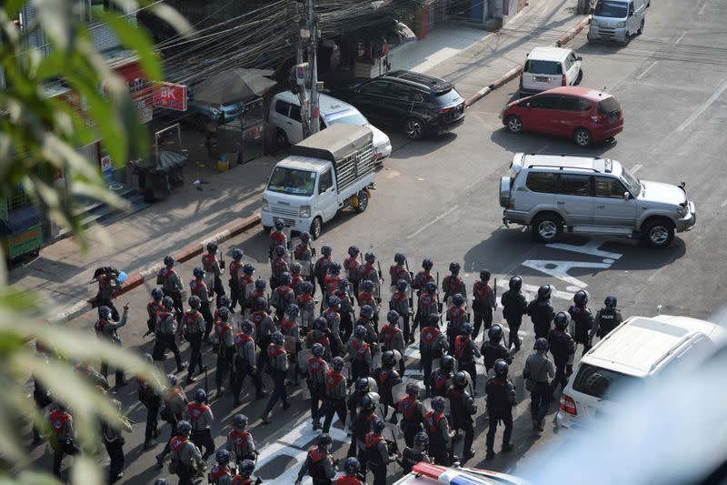FILE PHOTO: Riot police walk in the middle of a street during a protest against the military coup in Yangon