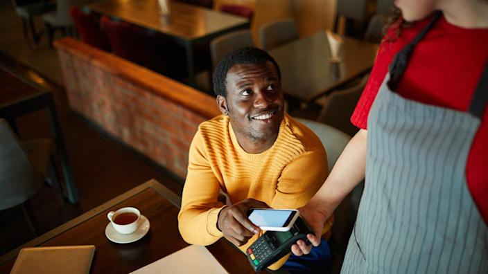 Young smiling man sitting by table and looking at waitress while paying for his order through smartphone.
