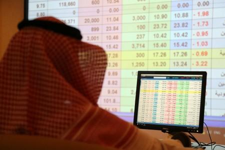 A saudi man looks to the computer showing stock prices at ANB Bank, in Riyadh