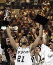 FILE - In this June 23, 2005, file photo, San Antonio Spurs' Tim Duncan (21) holds his MVP trophy, left, and the NBA basketball Championship trophy, right, after San Antonio won 81-74 to winGame 7 of the NBA finals in San Antonio. Joining Kobe Bryant as first-time finalists for the Basketball Hall of Fame are: 15-time All-Star Duncan, fellow 15-time All-Star Kevin Garnett and 10-time WNBA All-Star and four-time Olympic gold medalist Tamika Catchings. (AP Photo/Eric Gay, File)