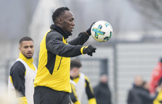 Jamaica's former sprinter Usain Bolt, center, takes part in a practice session of the Borussia Dortmund soccer squad in Dortmund, Germany, Friday, March 23, 2018. (Guido Kirchner/dpa via AP)