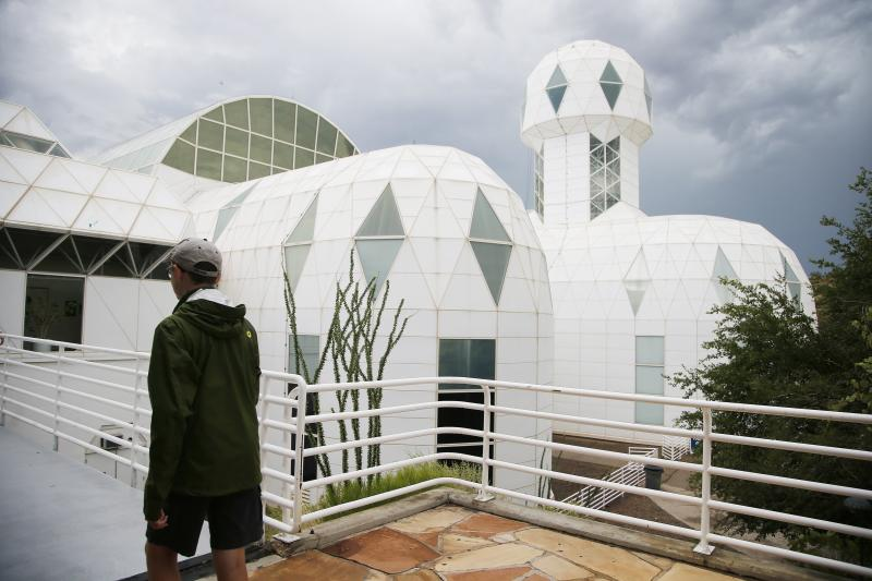 In this July 31, 2015 photo, a tourist walks to the main entrance of the Biosphere 2 facility while on a walking tour in Oracle, Ariz. University of Arizona officials say that 25 years after that New Age-style experiment in the Arizona desert, the glass-covered greenhouse thrives as a singular site for researchers from around the world studying everything from the effects of the ocean's acidification on coral to ways of ensuring food security. (AP Photo/Ross D. Franklin)