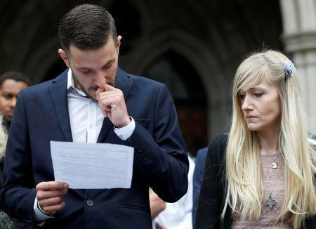 FILE PHOTO Charlie Gard's parents Connie Yates and Chris Gard read a statement at the High Court after a hearing on their baby's future, in London, Britain July 24, 2017. REUTERS/Peter Nicholls/File Photo