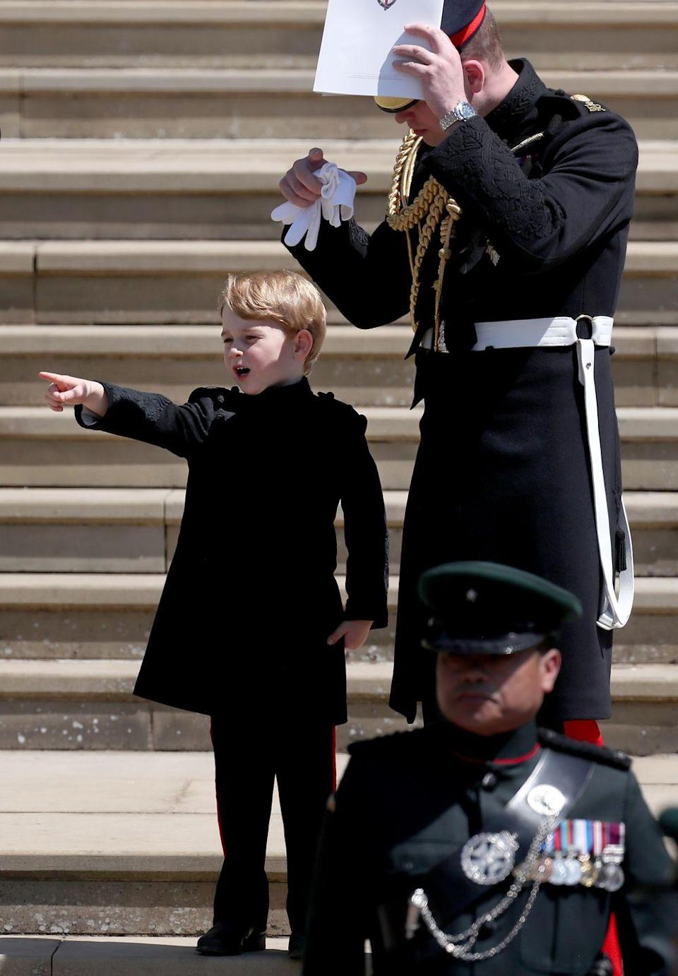 """<p>Prince George excitingly points to show something to his father Prince William outside of St. George's Chapel at Windsor Castle after the wedding of <a href=""""https://www.cosmopolitan.com/entertainment/g20760206/royal-wedding-secrets/"""" rel=""""nofollow noopener"""" target=""""_blank"""" data-ylk=""""slk:Prince Harry and Meghan Markle in May 2018"""" class=""""link rapid-noclick-resp"""">Prince Harry and Meghan Markle in May 2018</a>. The best part? They're wearing matching pants! Too cute.</p>"""