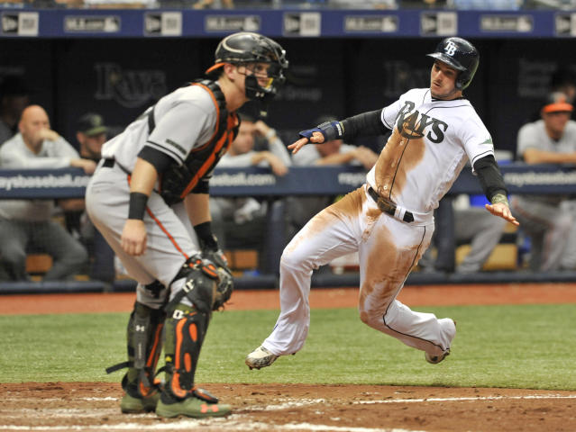 Tampa Bay Rays' Daniel Robertson, right, scores ahead of the throw to Baltimore Orioles catcher Chance Sico, left, during the third inning of a baseball game Sunday, May 27, 2018, in St. Petersburg, Fla. Robertson scores on Christian Arroyo's two-run single off Baltimore starter Kevin Gausman. (AP Photo/Steve Nesius)