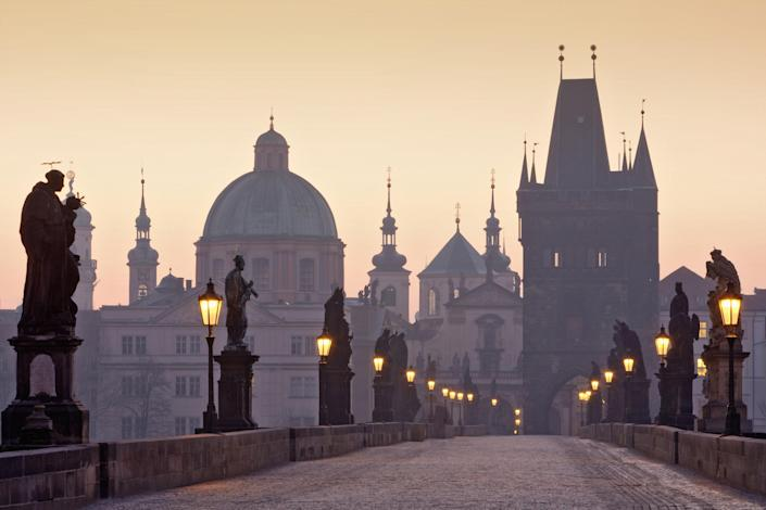 The Charles Bridge, which was completed in the early 1400s, is a historic bridge that crosses the Vltava river in Prague, Czech Republic. Built entirely of stone, the bridge nearly stretches 1,700 feet and is decorated with dozens of statues on both sides.