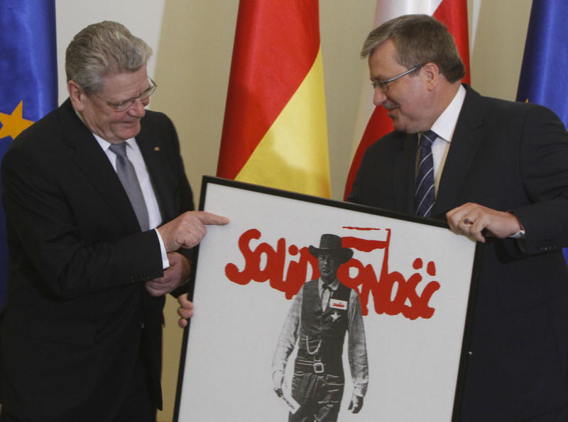 Poland's President Bronislaw Komorowski, right, hands over an original historic Solidarity poster to the new German President Joachim Gauck, in Warsaw, Poland, on Tuesday March 27, 2012. Gauck, 72, is a former East German pro-democracy activist and Lutheran minister who was elected March 18 and inaugurated Friday. German leaders in recent years have sometimes chosen Poland for their first trips abroad, a symbolic gesture stressing the strong alliance that has developed between the nations in the decades since Germany invaded and occupied Poland during World War II. (AP Photo/Czarek Sokolowski)