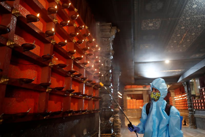 A man in personal protective equipment sanitizes a temple before they reopen for the public amid the spread of the coronavirus disease (COVID-19) in Mumbai