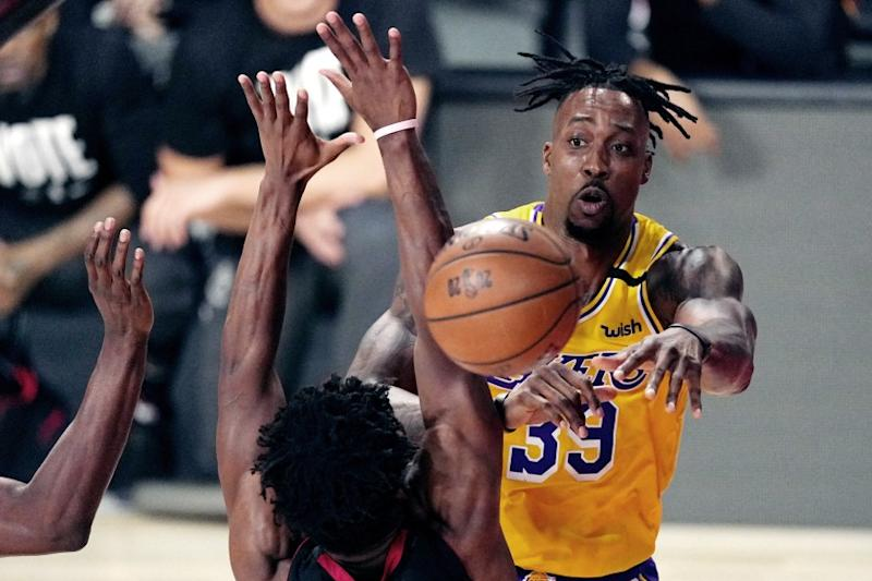 Los Angeles Lakers' Dwight Howard (39) passes the ball while pressured by the Miami Heat.