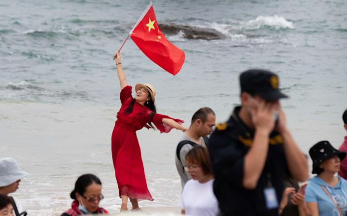 A woman holds up the Chinese national flag as people gather to watch the the launch of the Long March 5B rocket carrying China's Tianhe space station  - MATJAZ TANCIC/Shutterstock