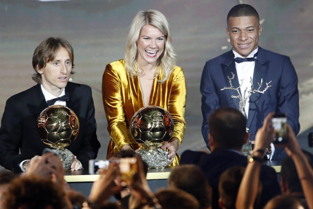 Olympique Lyonnais' Ada Hegerberg with the Women's Ballon d'Or, center, poses with Real Madrid's Luka Modric, with the Ballon d'Or, left, and Paris St Germain's Kylian Mbappe with the Kopa Trophy, right, during the Golden Ball award ceremony at the Grand Palais in Paris, France, Monday, Dec. 3, 2018. Awarded every year by France Football magazine since Stanley Matthews won it in 1956, the Ballon d'Or, Golden Ball for the best player of the year will be given to both a woman and a man. (AP Photo/Christophe Ena)
