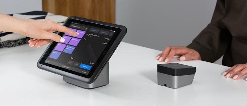 A merchant entering a sale on a tablet-based point-of-sale system, while a customer waits.