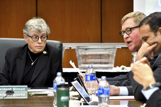 Michigan State Trustee Brian Breslin, second from right, addresses the board and onlookers as the board of trustees meeting Friday morning, Dec 15, 2017, in East Lansing, Mich. Listening at left is MSU president Lou Anna K. Simon. (AP)