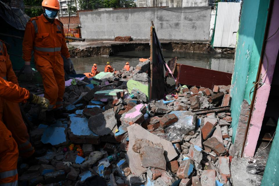 National Disaster Response Force personnel inspect the remains of a shanty house after it collapsed into a canal due to heavy rains in New Delhi on July 19, 2020. (Photo by Sajjad HUSSAIN / AFP) (Photo by SAJJAD HUSSAIN/AFP via Getty Images)